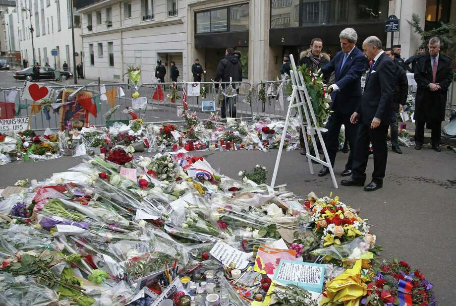 U.S. Secretary of State John Kerry and French Foreign Minister Laurent Fabius, right, lay a wreath at the site of the Charlie Hebdo newspaper terrorist attack in Paris, Friday, Jan. 16, 2015. U.S. Secretary of State John Kerry paid his respects Friday to the victims of last week's terrorist attacks in Paris in a show of American solidarity with the French people. (AP Photo/Michel Euler) Photo: AP / AP