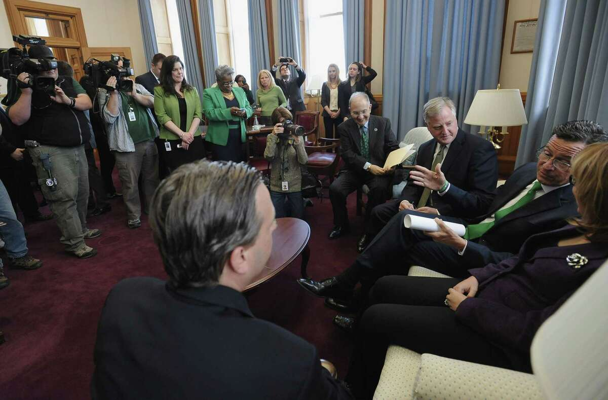 Former Arizona U.S. Rep. Gabby Giffords, right, sits with Connecticut Gov. Dannel P. Malloy at a meeting prior to a news conference at the state Capitol, Tuesday, March 17, 2015, in Hartford, Conn. Giffords to help promote the latest gun control proposals offered since the Newtown school shootings.