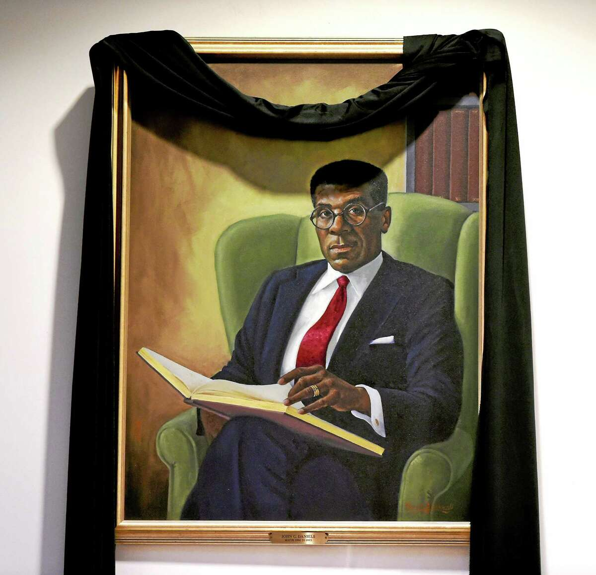 Black bunting is draped around the New Haven City Hall portrait of late New Haven Mayor John Daniels.