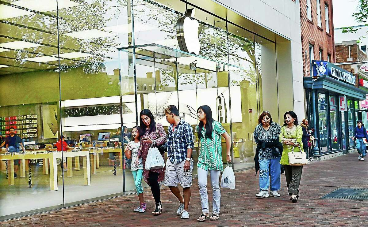 Shoppers walk by the Apple Store on Broadway in New Haven.