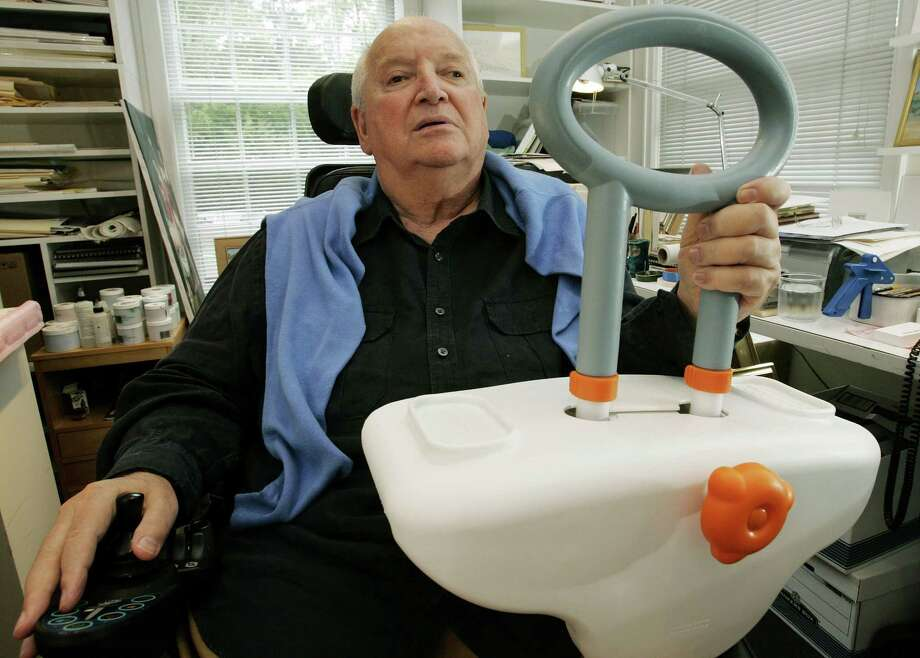 In this Sept. 11, 2009 file photo, architect and designer Michael Graves sits in his Princeton, N.J. studio holding a bathtub handle he designed to help the handicapped and elderly. Graves, who designed modern and whimsical postmodern structures and later household goods sold at Target stores has died in New Jersey. He was 80 years old. AP Photo/Mel Evans Photo: AP / AP