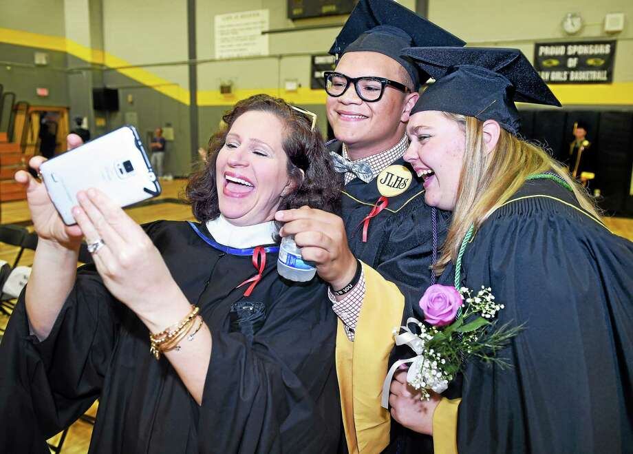From left, visual arts teacher Rachael Murphy, Nelson Vazquez and Barbara Perugini take a selfie in the gymnasium of Jonathan Law High School before graduation ceremonies Monday in Milford. Photo: Arnold Gold — New Haven Register