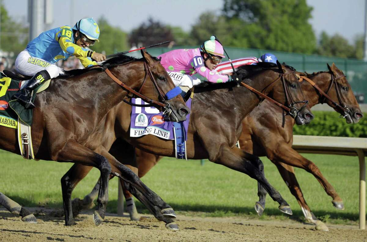 Jockey Gary Stevens (10) and Firing Line lead eventual winner American Pharoah, ridden by Victor Espinoza, left, during the 141st running of the Kentucky Derby on May 2 at Churchill Downs in Louisville, Ky.