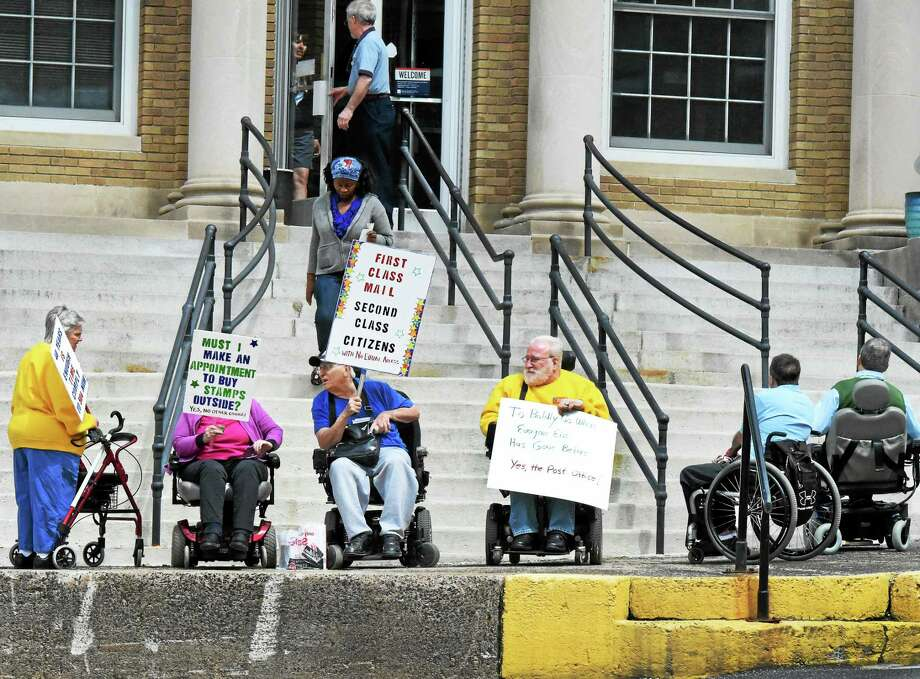 Irene Puccino of East Haven, left, president of the Center for Disability Rights board of directors, and Joe Luciano of Seymour, third from left, who helped organize the event, attend a rally outside the Seymour post office Wednesday. Photo: Peter Hvizdak — New Haven Register    / ©2015 Peter Hvizdak