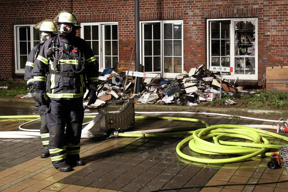 Firefighters stand outside the building of the 'Hamburger Morgenpost' in Hamburg, northern Germany, on Jan. 11, 2015. According to police, fire broke out in an archive room of the paper after an arson attack. Photo: AP Photo/dpa, Bodo Marks   / dpa