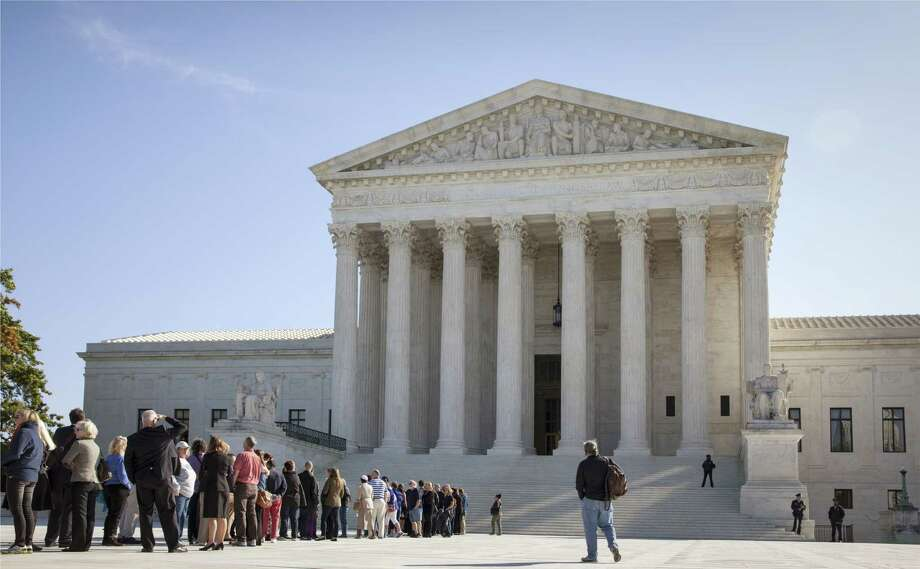 In this Oct. 6, 2014 photo, people wait to enter the Supreme Court in Washington. The Supreme Court could put the brakes on the Obama administration's growing crackdown against companies facing claims of discrimination against women, minorities and other protected groups. Photo: AP Photo/J. Scott Applewhite, File   / AP