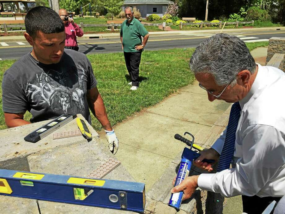 East Haven Mayor Joseph Maturo Jr., right, helps apply caulk to a brick as Phil Mauro, a worker with the town Public Works Department, observes on Monday at the Town Beach. Photo: Esteban L. Hernandez — New Haven Register