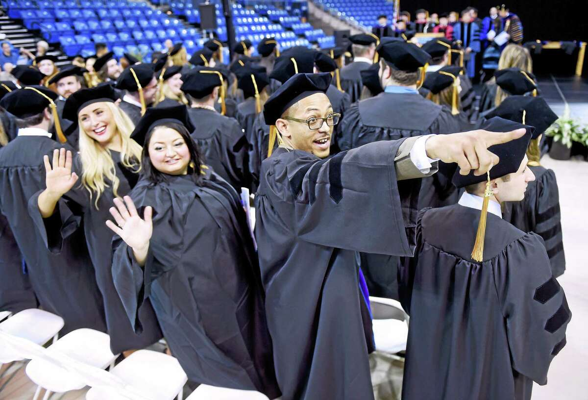 Left to right, Chelsea Vetre, Marissa McGill and Juan Sanchez wave to family at the commencement and doctoral hooding of the Quinnipiac University School of Law at the TD Bank Sports Cente.