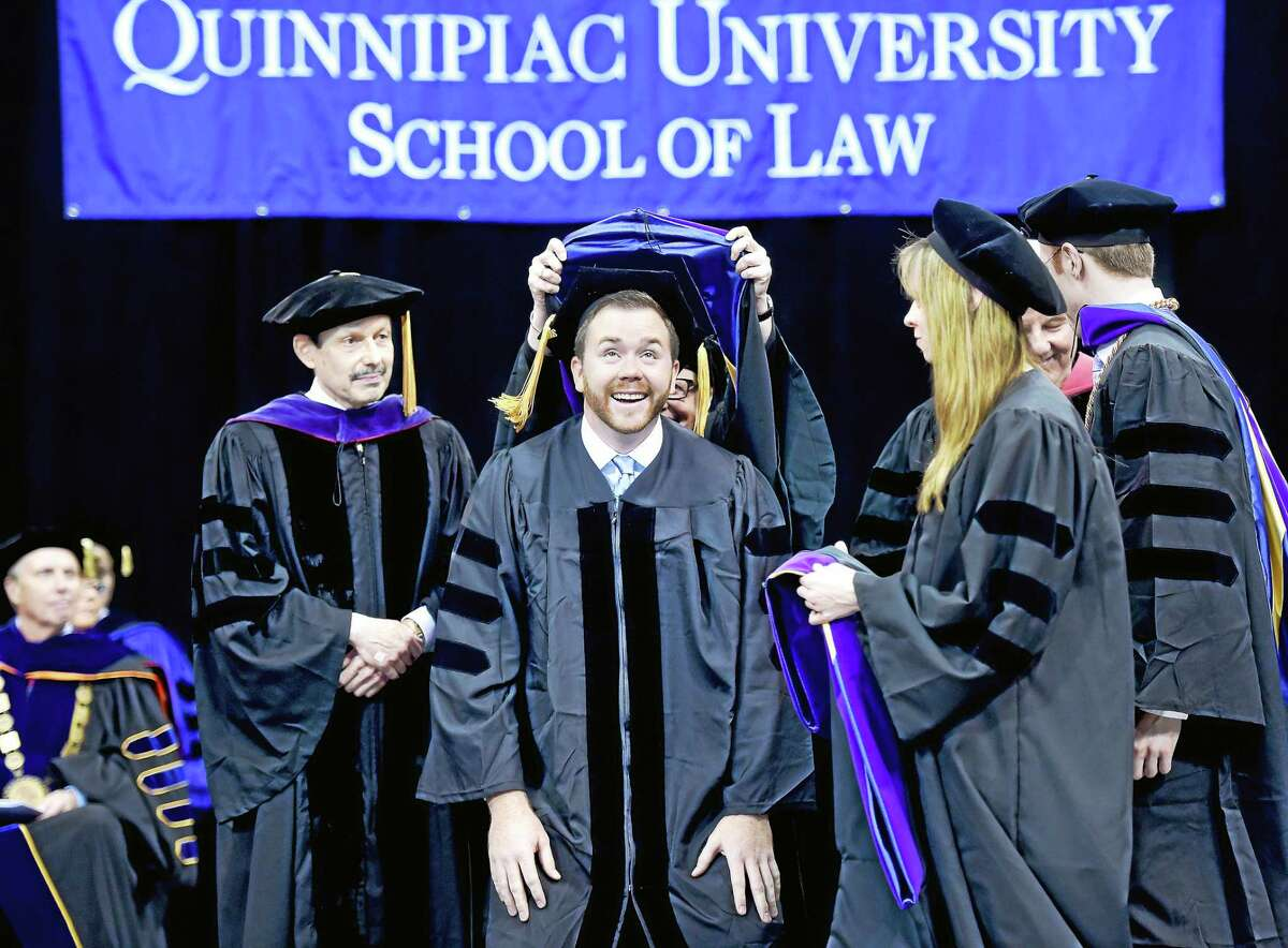 William Bennett (center) bends down as he is hooded by Professor Emerita Mary Ferrari at the Commencement and Doctoral Hooding of the Quinnipiac University School of Law at the TD Bank Sports Center Sunday.