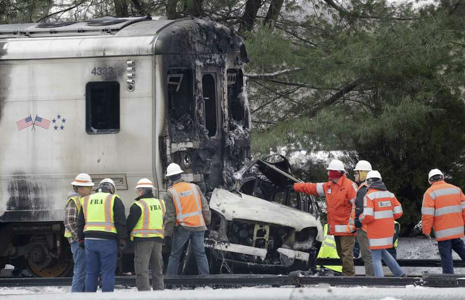 An investigator points to an SUV that was crushed and burned at the front of a Metro-North Railroad train, Wednesday, Feb. 4, 2015, in Valhalla, N.Y.  The commuter train slammed into the SUV stuck on the tracks Tuesday evening, killing the driver and at least five train passengers, authorities said. (AP Photo/Mark Lennihan) Photo: AP / AP