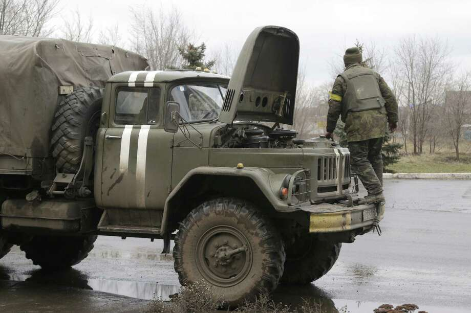 Ukranian government soldiers tries to fix his truck in Artemivsk, Ukraine, Wednesday, Feb. 4, 2015.  Soldiers bark orders at exhausted residents boarding evacuation buses with overflowing bags in hand, as another rebel artillery attack pummels this town on the front lines of Ukraineís separatist war. Despair is deepening for a shrinking population that has been without power, heating and running water for almost two weeks. The relentless rebel advance on the  railway town of Debaltseve is being slowed only by Ukrainian tanks, cannons and rocket launchers. (AP Photo/Petr David Josek) Photo: AP / AP
