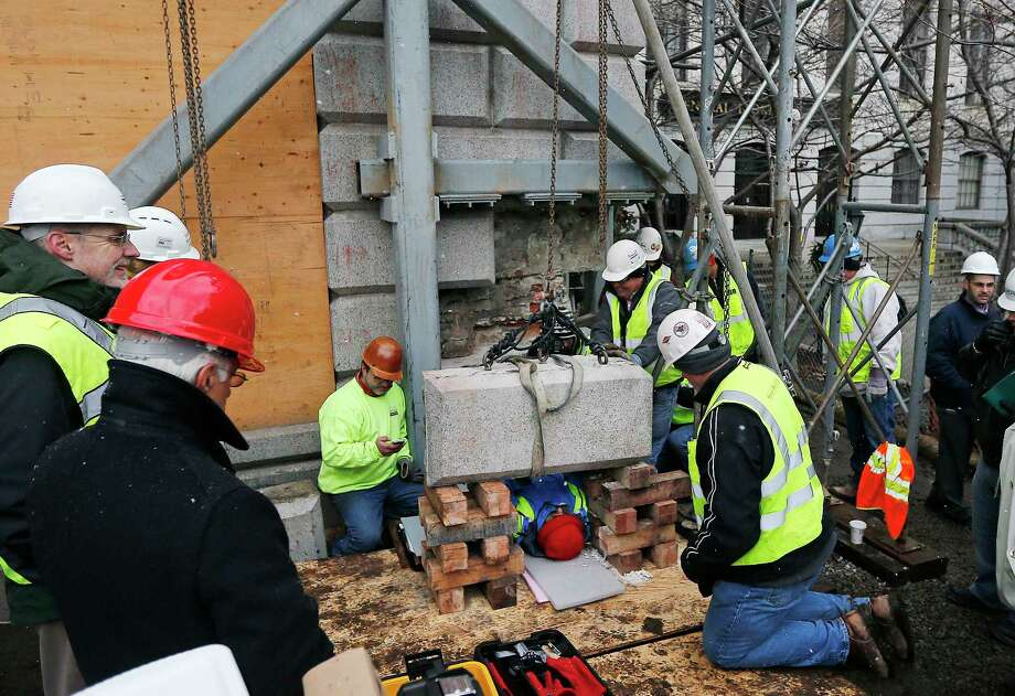 Massachusetts officials work Dec. 11 to remove a time capsule in the cornerstone of the Statehouse in Boston. Secretary of State William Galvin says the 200-year-old time capsule is believed to contain items such as old coins and newspapers, but the condition of the contents isnít yet known. Photo: Associated Press   / AP