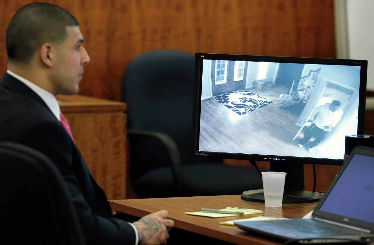 Former New England Patriots NFL football player Aaron Hernandez looks on as a still image from a June 17, 2013 surveillance video from his home is displayed on a monitor during his murder trial on April 2, 2015, in Fall River, Mass.