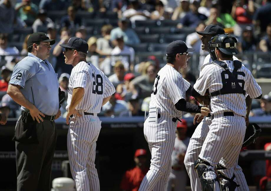 Teammates hold back Yankees starting pitcher CC Sabathia, right, as manager Joe Girardi, second from left, argues with umpire Dan Bellino, left, during the sixth inning. Photo: Seth Wenig — The Associated Press   / AP