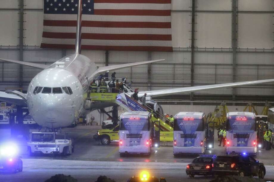 Members of the New England Patriots disembark from an aircraft inside a hangar at Logan International Airport on Monday in Boston. Photo: Steven Senne — The Associated Press   / AP