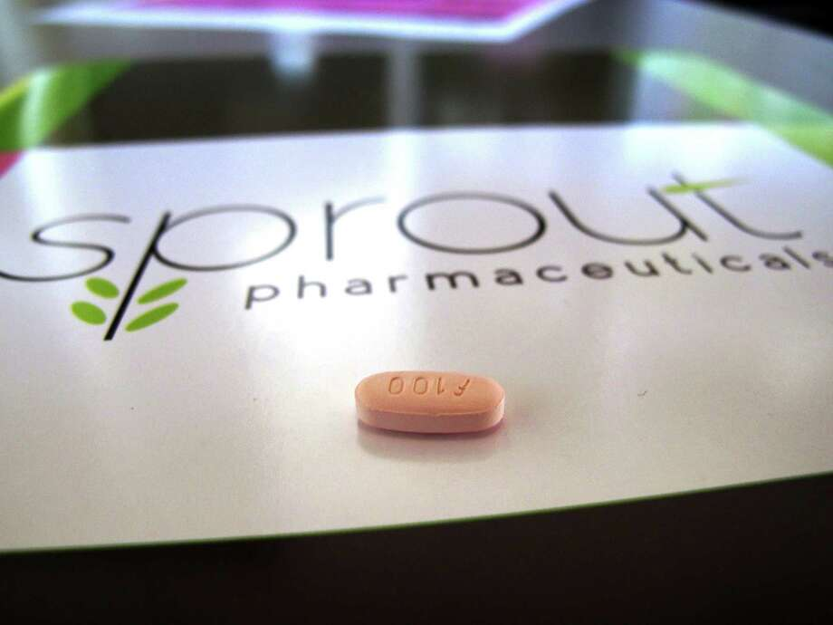 A tablet of flibanserin sits on a brochure for Sprout Pharmaceuticals in the company's Raleigh, N.C., headquarters. Government health experts on Thursday, June 4, 2015 backed the approval of the experimental drug intended to boost the female sex drive, but stress that it should carry safety restrictions to manage side effects including fatigue, low blood pressure and fainting. Photo: AP Photo/Allen G. Breed, File   / AP