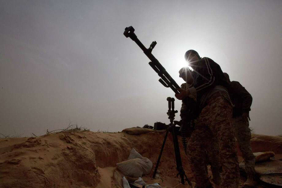 In this Feb. 21, 2015 photo, Libyan soldiers try to fix a weapon that jammed during clashes with militants on the frontline in Al Ajaylat, 120 kilometers (75 miles) west of Tripoli, Libya. Army forces in Libya have been fighting Islamic and tribal militias since last September. Photo: AP Photo/Mohamed Ben Khalifa   / AP