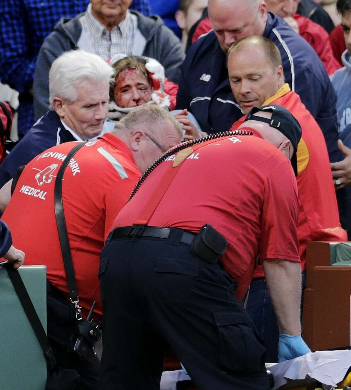 A fan, who was hit in the head with a broken bat by the Oakland Athletics' Brett Lawrie, is helped from the stands during Friday night's game at Fenway Park in Boston.