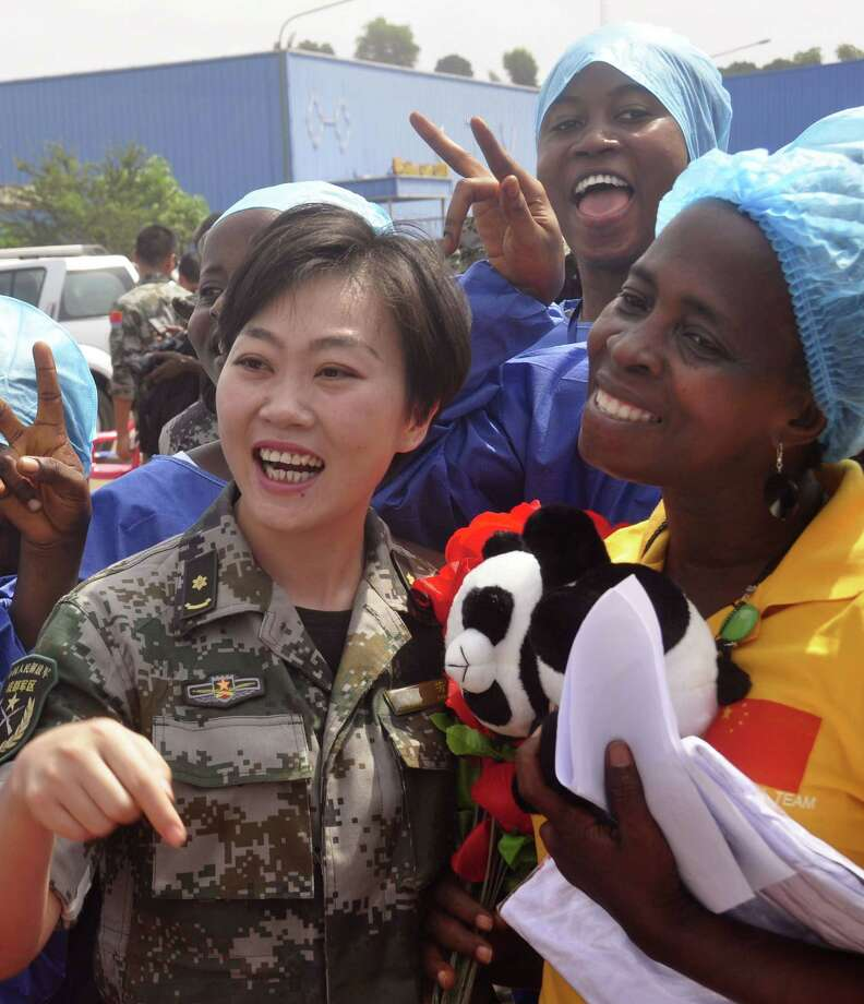 Ebola patient Beatrice Yardolo, right, celebrate with a Chinese military health workers and others  as she leaves the Chinese Ebola treatment center were she was treated for the Ebola virus infection outskirts of Monrovia, Liberia, Thursday, March 5, 2015.  Liberia released its last Ebola patient, a 58-year old English teacher, from a treatment center in the capital on Thursday, beginning its countdown to being declared Ebola free. 'I am one of the happiest human beings today on earth because it was not easy going through this situation and coming out alive,' Beatrice Yardolo told The Associated Press after her release. She kept thanking God and the health workers at the center.(AP Photo/ Abbas Dulleh) Photo: AP / AP