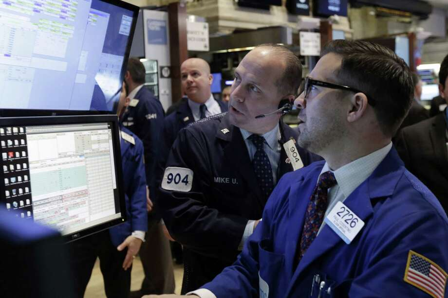 Trader Michael Urkonis, center, and specialist Paul Cosentino, right, work on the floor of the New York Stock Exchange Thursday. Photo: Richard Drew — The Associated Press   / AP