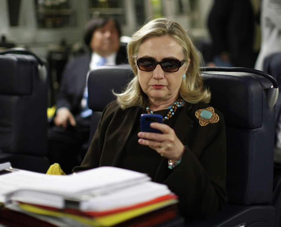 In this Oct. 18, 2011, file photo, then-Secretary of State Hillary Rodham Clinton checks her Blackberry from a desk inside a C-17 military plane upon her departure from Malta, in the Mediterranean Sea, bound for Tripoli, Libya. Photo: AP File Photo   / REUTERS POOL