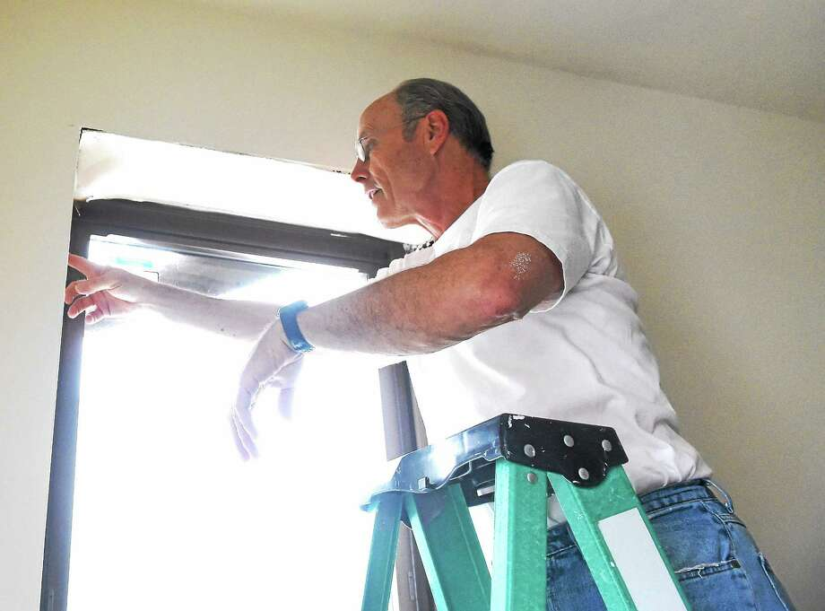 Lyle Holmberg of the First Congregational Church of Madison inspects a window leak in a Christian Community Action apartment house in the Hill Neighborhood section of New Haven recently. Photo: (Peter Hvizdak - New Haven Register)   / ©2015 Peter Hvizdak