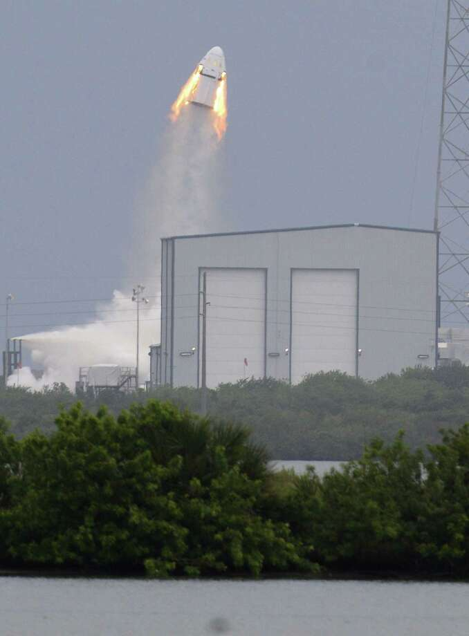 A SpaceX Dragon mock-up capsule blasts into the air, Wednesday, May 6, 2015 during a test flight in Cape Canaveral, Fla. The unmanned flight was testing a new, super-streamlined launch escape system for astronauts. The California-based company led by billionaire Elon Musk aims to launch U.S. astronauts to the International Space Station as early as 2017. (Craig Bailey/Florida Today via AP)  NO SALES, MAGS OUT Photo: AP / Florida Today