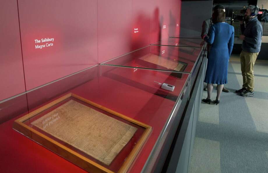 Members of the media film four of the original surviving Magna Carta manuscripts that have been brought together by the British Library for the first time, during a media preview in London on Feb. 2, 2015. Photo: AP Photo/Alastair Grant   / AP