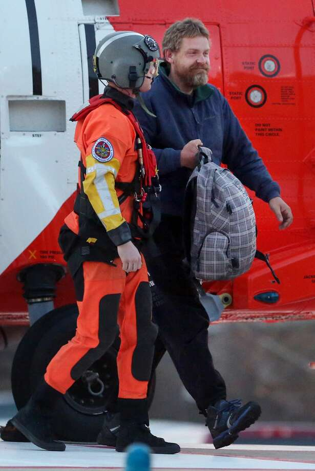 FILE - In this Thursday, April 2, 2015, file photo, Louis Jordan, right, walks from a Coast Guard helicopter to the Sentara Norfolk General Hospital in Norfolk, Va., after being found off the North Carolina coast. Jordan, who was reported missing at sea two months ago, was rescued on the overturned hull of his sailboat, and he walked away from a hospital hours later in good condition, with no signs of sunburn, dehydration or other ailments. (AP Photo/The Virginian-Pilot, Steve Earley, File) Photo: AP / The Virginian-Pilot