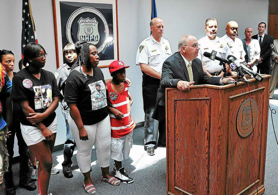 Achilles Generoso, assistant police chief, detective division, speaks to the media about the arrest of Ricardo Myers of Bridgeport in the shooting death of Tirrell Drew. At left is Drew's family. Photo: Peter Casolino — NEW HAVEN Register File Photo