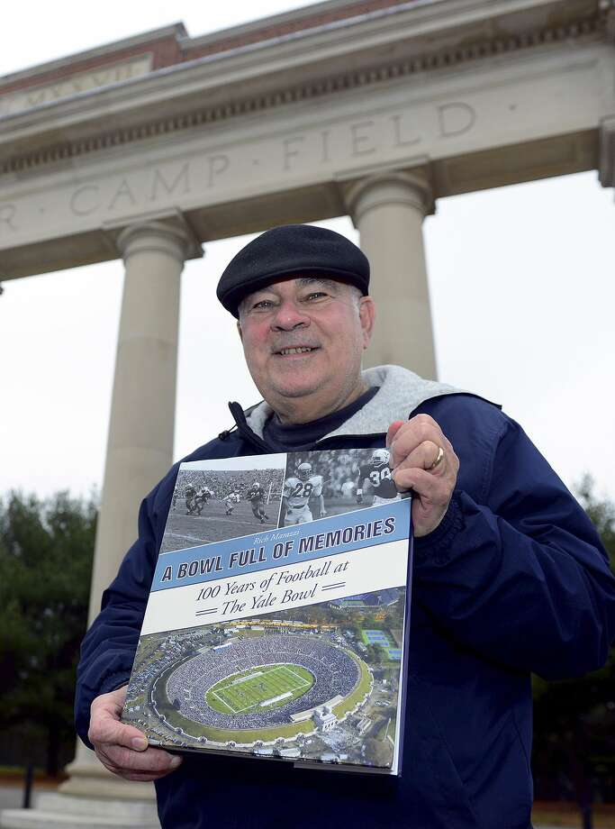 """In this Dec. 16, 2014 photo, Richard Marazzi displays """"Bowl Full of Memories,"""" the coffee table book he authored, in front of the Yale Bowl's Walter Camp Field entrance in New Haven. (AP Photo/Hearst Connecticut Media/Connecticut Post, Christian Abraham) Photo: AP / Connecticut Post"""