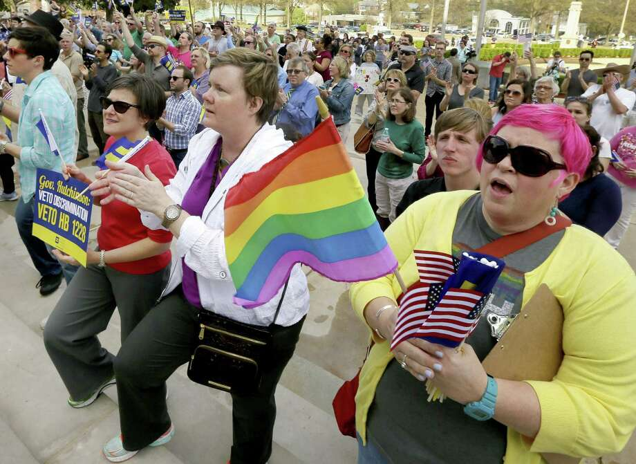 In this March 31, 2015 file photo, Barbara Hall, right, of Little Rock, joins others at a rally against a new religious objections law outside the Capitol in Little Rock, Ark. The national focus on whether new religious objections laws in Indiana and Arkansas could be used to discriminate against gays and lesbians has boosted efforts for broader civil rights law protections in those and other states. (AP Photo/Danny Johnston, File) Photo: AP / AP