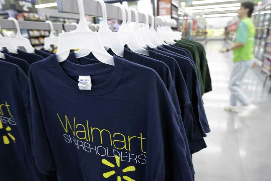 A man walks by a display of Wal-mart Shareholders shirts for sale at a Wal-mart Neighborhood Market in Bentonville, Ark., Thursday, June 4, 2015. Wal-mart shareholders and employees are gathered in northwest Arkansas for annual meeting scheduled for Friday, June 5. (AP Photo/Danny Johnston) Photo: AP / AP