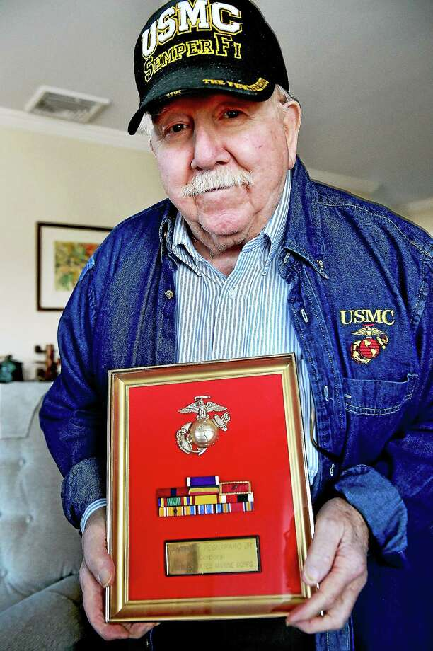 WWII veteran retired cpl. Anthony Pegnataro, Jr. holds his U.S. Marine Corps Ribbon Bars in the livingroom of his home in Branford, Wednesday, April 1, 2015. Photo: Catherine Avalone - New Haven Register      / New Haven RegisterThe Middletown Press