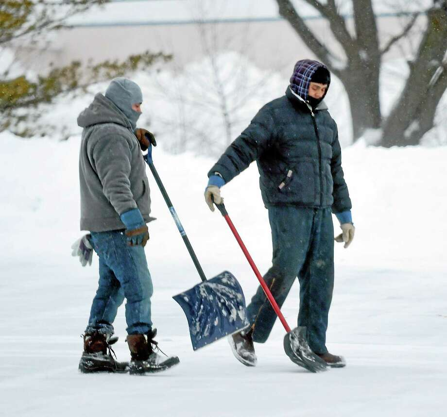 Shovelers walk across the parking lot of the Connecticut Post Mall in Milford Monday morning 2/2/2015. Photo: (Arnold Gold-New Haven Register)