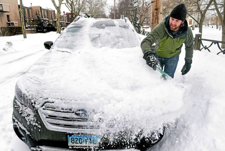 (Arnold Gold-New Haven Register)  Jared Verrillo clears his wife's car of snow in Wooster Square in New Haven on 2/2/2015. Photo: Journal Register Co.