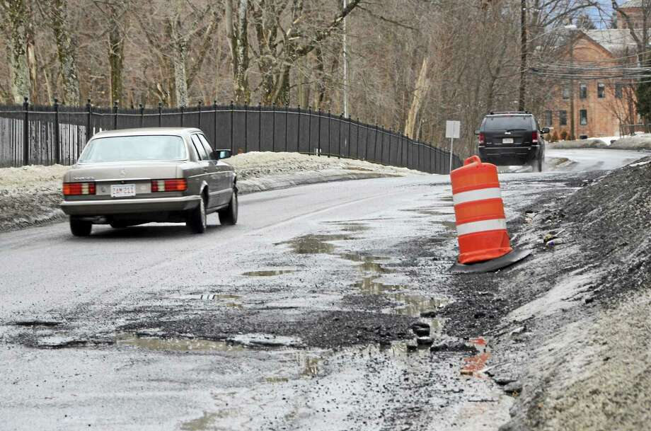 A motorist drives into the left lane to avoid potholes on Pecks Road in Pittsfield on Monday. March, 16, 2015. Gillian Jones — The Berkshire Eagle Photo: Gillian Jones — The Berkshire Eagle