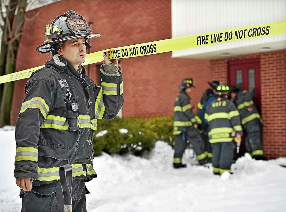 Firefighter Freddy Lopez of Engine 10 helps set up the fire line around the exterior of 116 Welton St. in New Haven, where a roof partially collapsed due to the weight of ice and snow Wednesday. Photo: Catherine Avalone _ New Haven Register    / New Haven RegisterThe Middletown Press