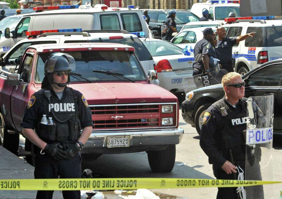 Police stand behind tape Monday, May 4, 2015, in Baltimore. Lt. Col. Melvin Russell said police pursued a man who was spotted on surveillance cameras and appeared to be armed with a handgun. Police said the man was taken into custody after a brief chase, during which a gunshot was heard. (Amy Davis/The Baltimore Sun via AP) Photo: AP / The Baltimore Sun