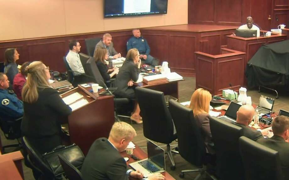 FILE - In this image taken from Colorado Judicial Department video, Colorado theater shooter James Holmes, left rear in light-colored shirt, watches during testimony by witness Derick Spruel, upper right, on the second day of his trial in Centennial, Colo., Monday, April 27, 2015. Standing at left is prosecutor Lisa Teesch-Maguire. Defense attorneys have urged jurors not to let emotions sway them, but with weeks of harrowing testimony still to come, experts say James Holmesí lawyers will have a difficult time convincing jurors to put sympathy behind them as they decide whether he was legally insane when he killed 12 people and injured 70 others in July 2012. (Colorado Judicial Department via AP, Pool, File) Photo: AP / POOL Colorado Judicial Department