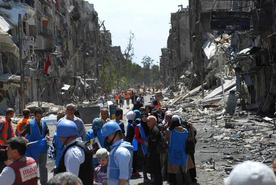 This picture taken on Thursday, April. 24, 2014 and provided by the United Nations Relief and Works Agency for Palestine Refugees in the Near East (UNRWA), U.N relief workers with blue helmets and vests stand next of residents of the besieged Palestinian camp of Yarmouk, right, who stand in line to receive aid food distributed by UNRWA, on the southern edge of the Syrian capital Damascus, Syria. Photo: AP Photo/UNRWA, File   / Unrwa.org