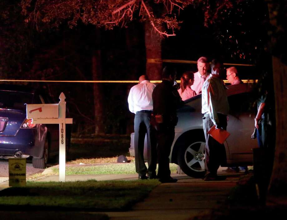 In this photo taken Jan. 21, 2015, investigators gather outside an East Lake, Fla., home, where authorities say a two-year-old child died from an apparent self-inflicted gunshot wound. Photo: AP Photo/The Tampa Bay Times, Douglas R. Clifford   / The Tampa Bay Times