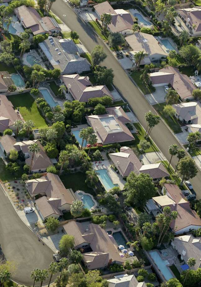 Homes with swimming pool line the streets of this neighborhood Friday, April 3, 2015 in Palm Springs, Calif. California Gov. Jerry Brown ordered officials Wednesday to impose statewide mandatory water restrictions for the first time in history as surveyors found the lowest snow level in the Sierra Nevada snowpack in 65 years of record-keeping. Photo: (AP Photo/Chris Carlson) / AP