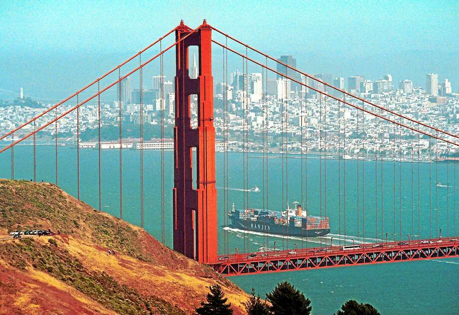 "The Golden Gate Bridge frames the San Francisco skyline as a ship passes beneath it in this view taken from the Marin Headlands near Sausalito, Calif., Wednesday, June 17, 1999.  A century and a half after the clarion cry of ""Gold, boys, gold!"" California today is a parade of clashing icons. It's a place of eggheads and Deadheads, hippies and hip-hop, a place where towheaded beach boys surf the waves and balding billionaires surf the Net, a place where dreamers push their visions of science and culture to the edge, and where losers wake in the gray dawn of reality to find they've gone over it.   As the sun sets on the 20th century, California is a state of mind. (AP Photo/Eric Risberg) Photo: ASSOCIATED PRESS / AP1999"