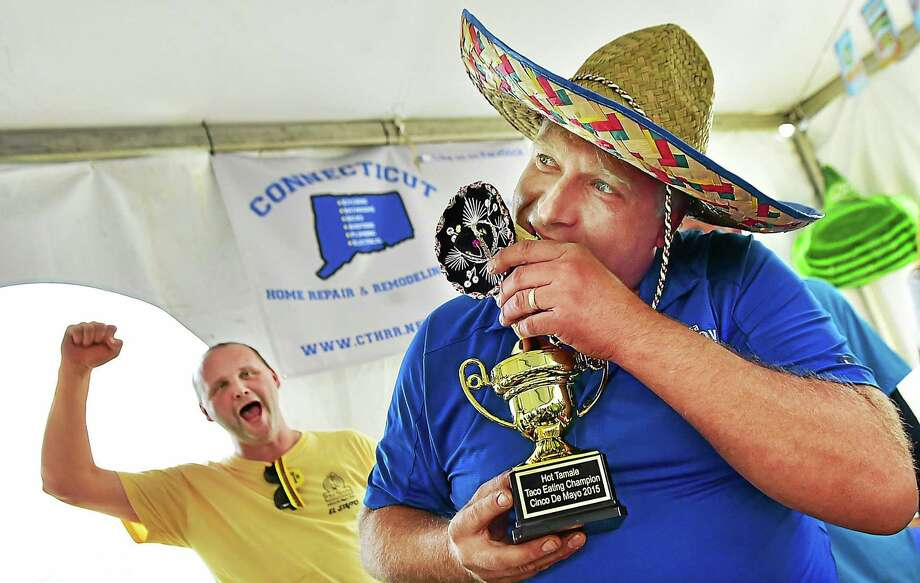 Seymour Land Trust President Alex Danka pretends to bite the plastic taco on the top of the championship trophy at the Cinco de Mayo Elected Officials' Taco-Eating Contest Tuesday, after downing 14 tacos to benefit TEAM, Inc.'s Meals on Wheels program. Photo: Catherine Avalone — New Haven Register    / New Haven RegisterThe Middletown Press