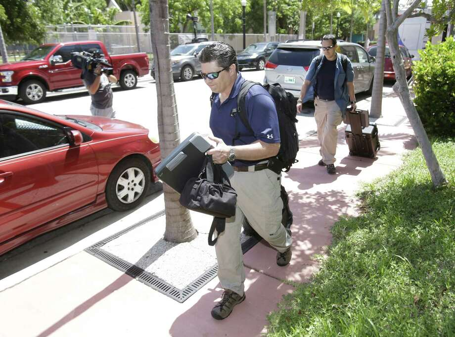 """Federal Bureau of Investigation agents leave the offices of the Confederation of North, Central America and Caribbean Association Football (CONCACAF,) Wednesday, May 27, 2015, in Miami Beach, Fla. Swiss prosecutors opened criminal proceedings into FIFA's awarding of the 2018 and 2022 World Cups, only hours after seven soccer officials were arrested Wednesday pending extradition to the U.S. in a separate probe of """"rampant, systemic, and deep-rooted"""" corruption. (AP Photo/Wilfredo Lee) Photo: AP / AP"""