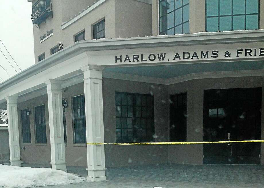 Police tape is visible at offices connected to a parking garage where two males were injured in a shooting Sunday at 1 New Haven Ave., Milford. Photo: (Pamela McLoughlin -- New Haven Register)