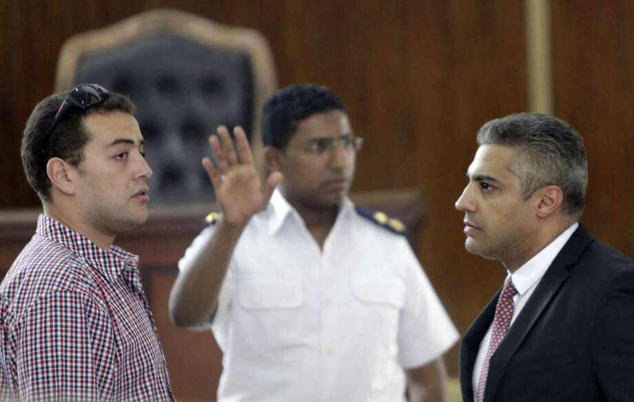 An Egyptian policeman directs Canadian Al-Jazeera English journalist Mohammed Fahmy, right, and his Egyptian colleague Baher Mohammed, left, as they wait for their retrial in front of a policeman at a courtroom in Tora prison, in Cairo, Egypt. Photo: AP Photo   / AP