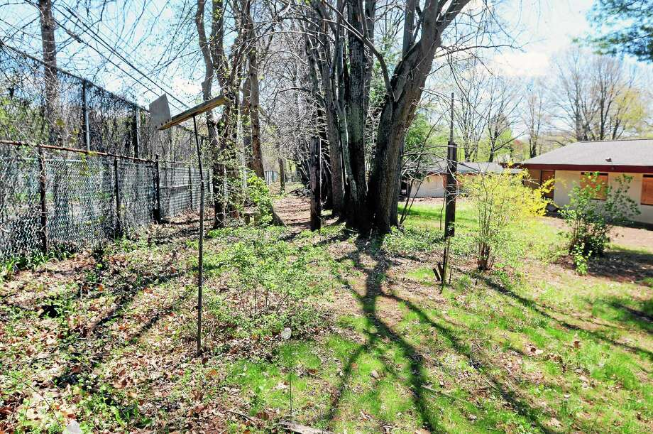 (Arnold Gold — New Haven Register)  The file photo from May 5, 2014, shows a tall fence separating the Abraham Ribicoff Cottages in New Haven and Woodin Street in Hamden. Photo: Journal Register Co.