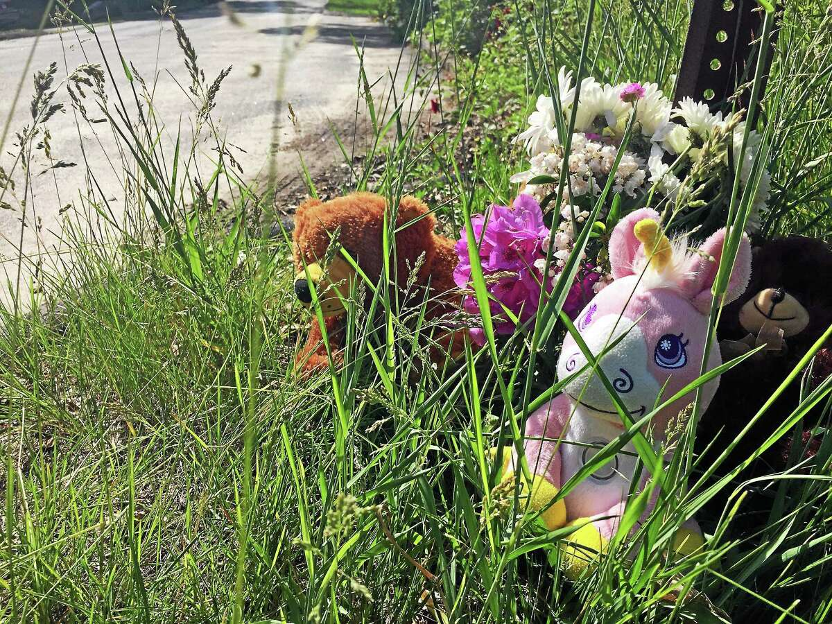 A makeshift memorial with flowers and plush toys sits outside a home on Strong Street in East Haven on Wednesday where two children were found dead the day before. An East Haven police officer on the scene said he wasn't sure what time the memorial had sprung up.